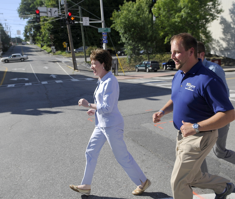 Sen. Susan Collins runs across Bridge Street in Augusta on Wednesday with state Rep. Matt Pouliot, R-Augusta, while campaigning in downtown Augusta.
