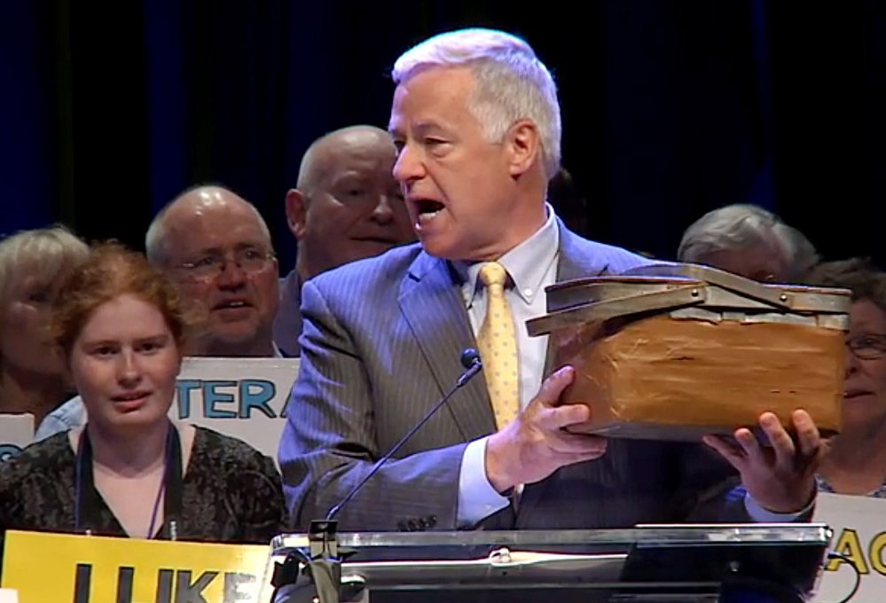 Rep. Mike Michaud holds his lunch bucket at the Democratic State Convention in Bangor last spring. He hopes to give it a new home in Augusta in January.