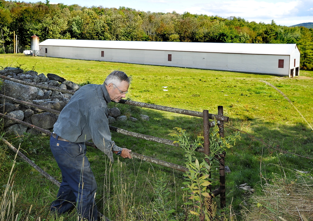 Russ Florenz closes the gate to a grazing pasture in Paris, where his unused 300-foot-long chicken barn will get 200 solar panels installed as part of the first community solar farm in Maine.