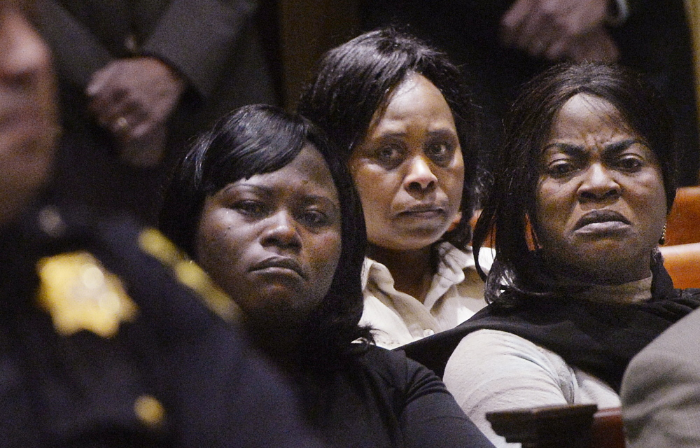 Women from the African immigrant community look toward Evaristo Deus on Friday as he arrives at a court hearing in 2014, where he was charged with the murder of Laudrinha Kubeloso. He was sentenced Tuesday.