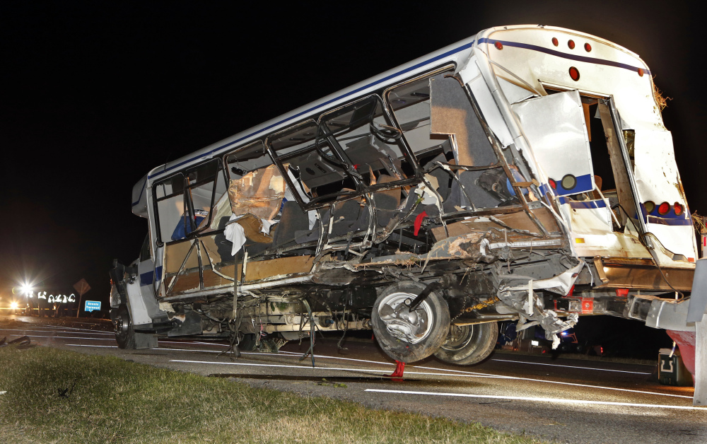 A wrecker removes the team bus as Oklahoma Highway Patrol and emergency personnel work the scene of an accident just south of the Turner Falls area on Saturday.  Four members of a Texas college softball team died after a tractor trailer crossed over the center median on Interstate 35 and collided with the team's bus Friday night.