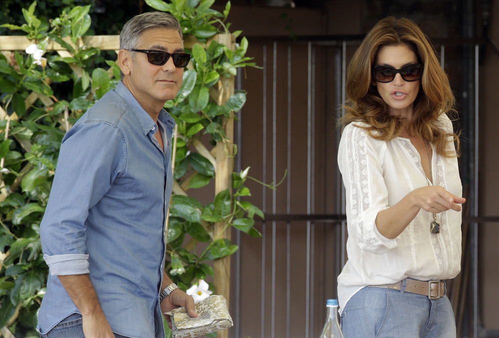 George Clooney and Cindy Crawford walk in the garden of the Cipriani hotel in Venice on Saturday. Clooney, 53, and Alamuddin, 36, were married Saturday in Venice.