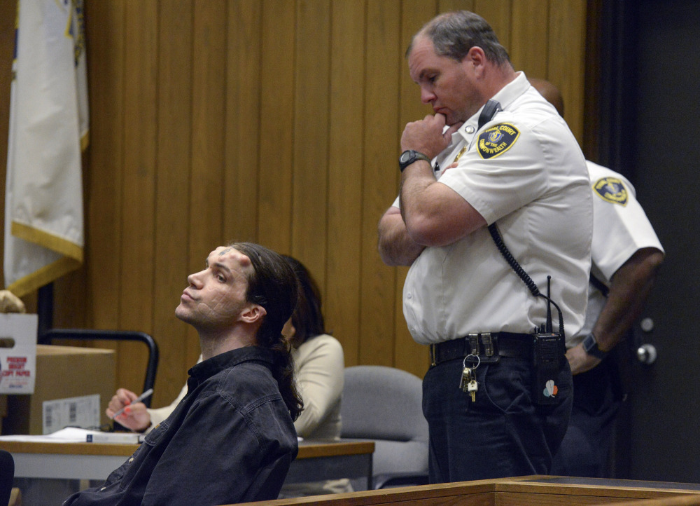 Caius Veiovis, seated, reacts to guilty verdicts in his triple-murder trial Friday in Hampden Superior Court in Springfield, Mass. He is the third of three defendants in the 2011 killings.