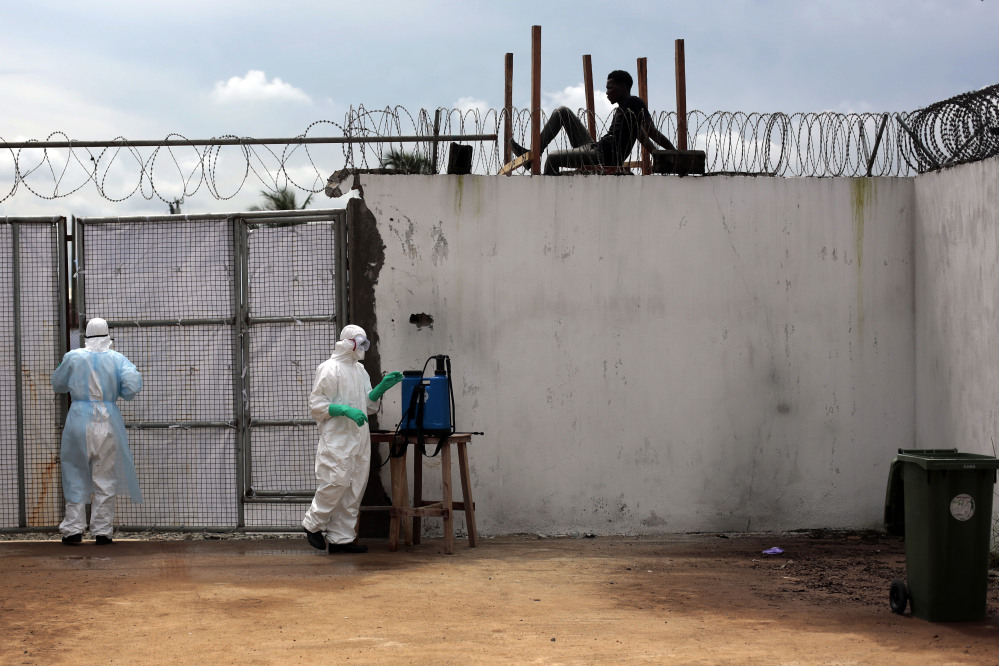Health workers stand outside the Island Clinic Ebola isolation and treatment center in Monrovia, Liberia, on Friday. The outbreak has overwhelmed the health care system.
