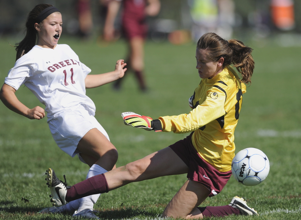 Freeport goalkeeper Izzy Qualls deflects a scoring bid by Ellie Schad of Greely during their Western Maine Conference girls' soccer game Saturday. Undefeated Greely won its seventh game with a 3-0 victory.