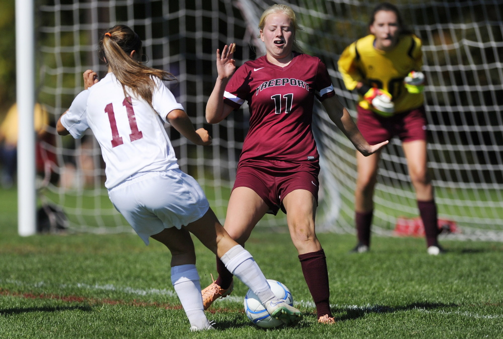 Ellie Schad of Greely looks for a way around defender Lindsay Cartmell of Freeport as goalkeeper Izzy Qualls prepares for a shot during their game in Cumberland Saturday. John Ewing/Staff Photographer