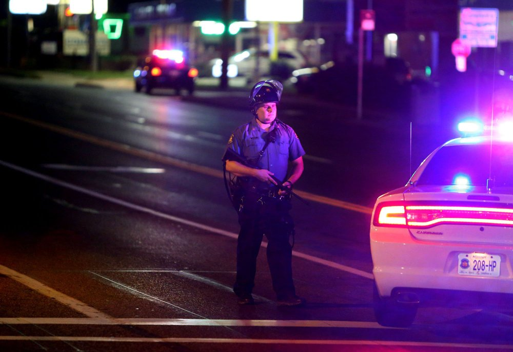 A police  officer stands at Chambers Road at West Florissant on Saturday in Ferguson, Mo.