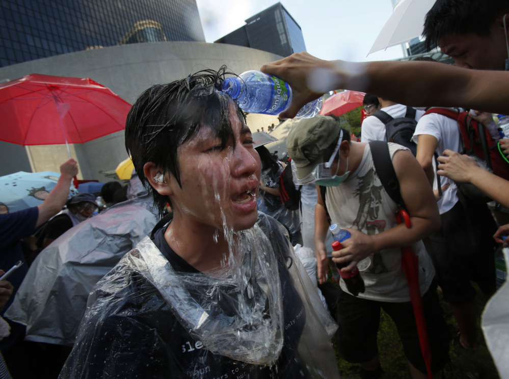 A student protester is overcome by pepper spray from anti-riot police as thousands of protesters surround the government headquarters in Hong Kong on Sunday.