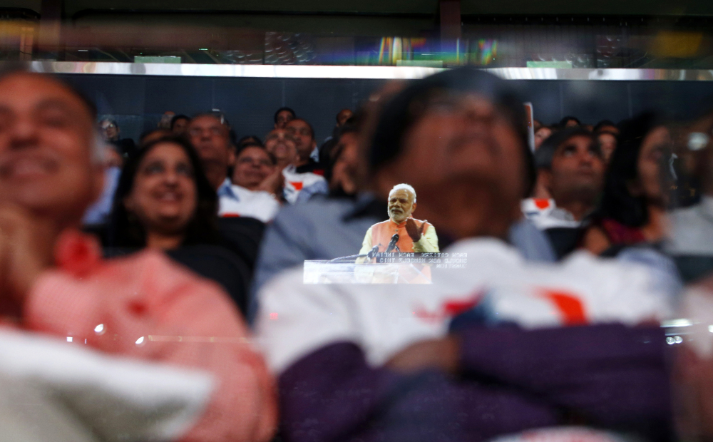 Prime Minister Narendra Modi of India is reflected in a glass barrier as he gives a speech at Madison Square Garden in New York on Sunday. About 30 U.S. lawmakers attended the event, which drew a crowd of 18,000.