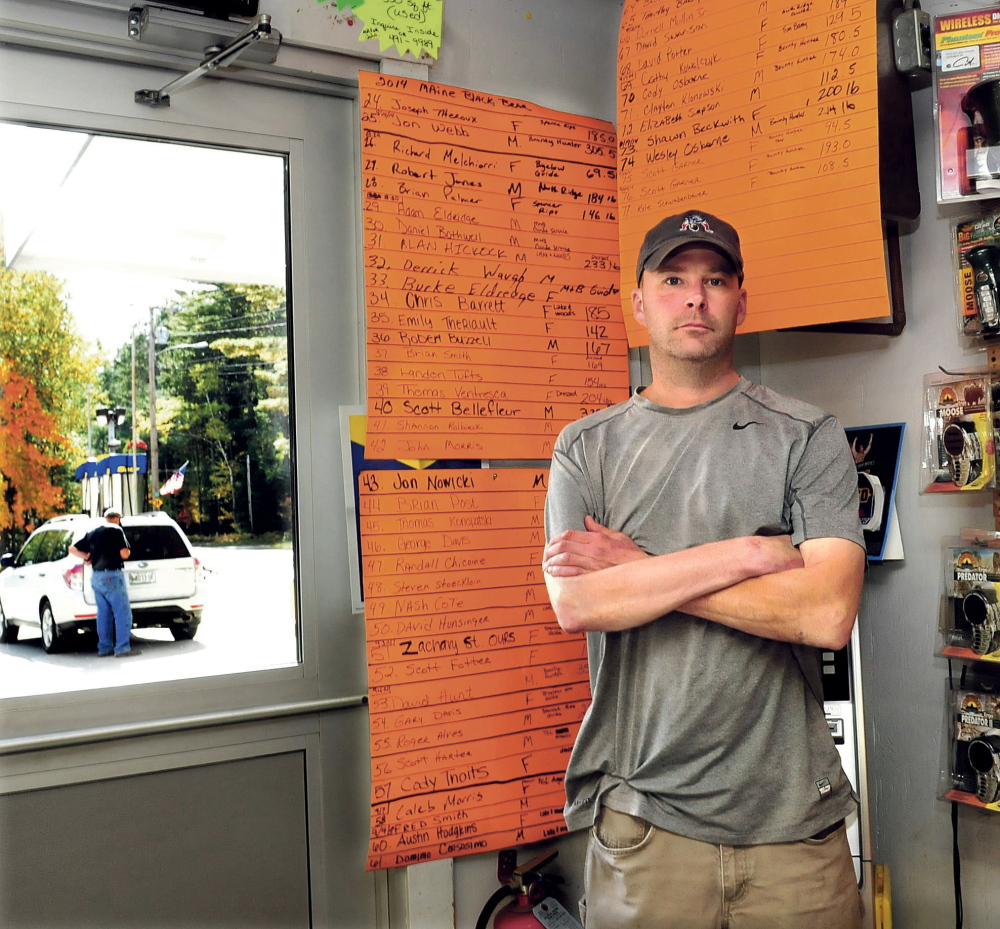 "As a customer pumps gasoline outside Pines Market in Eustis, owner John Morris stands beside the tally boards of the 77 bears that have been tagged this season. The number is twice the amount tagged last year. Morris said if the bear referendum passes it would have an adverse impact on his business. ""There are plenty of bear around this year,"" Morris said.  David Leaming/Morning Sentinel"