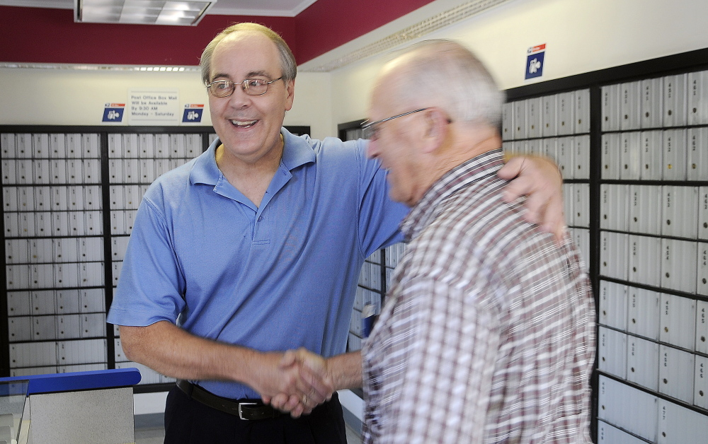 "Customer Dick Poulin, right, congratulates retiring Postmaster David Shepherd at the post office Monday. ""He takes care of the customers like you would not believe,"" Poulin said."