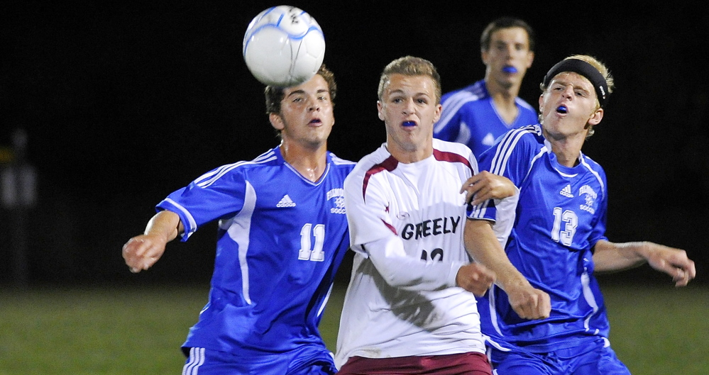 Falmouth, left, Jonah Spiegel, who eventually scored the game's only goal, and teammate John McConnell, right, battles Greely's Jacob Nason for the ball during the Yachtsmen's 1-0 win Monday in Cumberland.