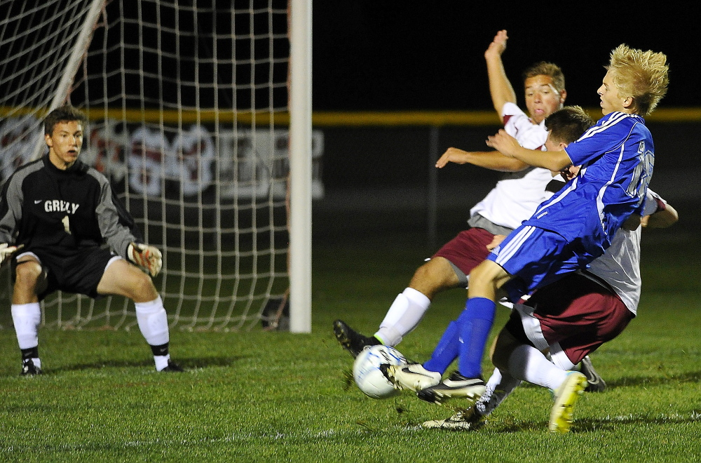 CUMBERLAND, ME - SEPTEMBER 29: Greely #1, goalkeeper John Wright keeps his eye on the ball as Falmouth #18, Mitchell Day, on a breakaway attack, gets tackled by two Greely defenders as Greely hosts Falmouth in Boys High School Soccer action. (Photo by Gordon Chibroski/Staff Photographer)