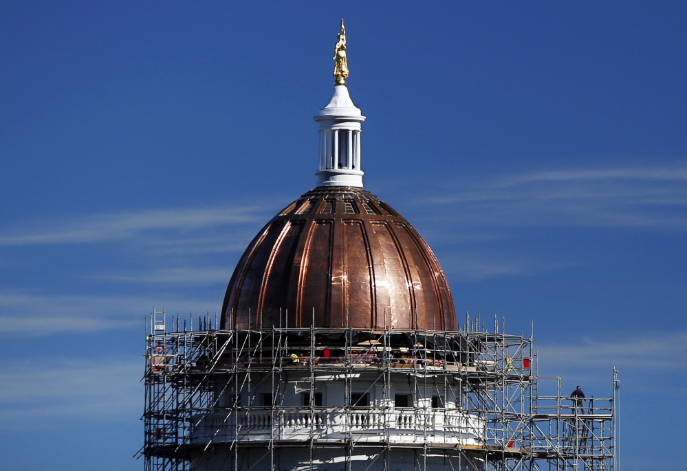 The new copper sheath shines on the State House dome during construction last month. Legislative leaders left a time capsule under the new copper.