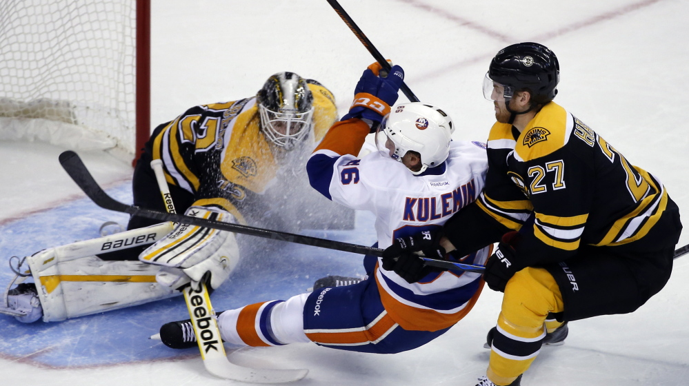 Nikolai Kulemin of the Islanders gets checked from behind by Bruins defenseman Dougie Hamilton in front of goalie Niklas Svedberg in the first period of Tuesday night's preseason game in Boston. The Islanders won 5-3 with two goals in the final 3:19 of the third period.