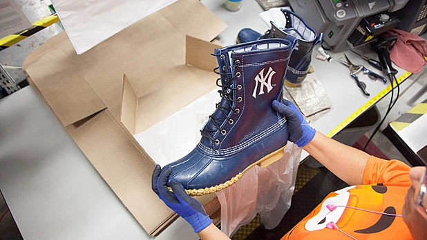 A worker at L.L.Bean holds up a pair of boots made specially for Derek Jeter of the Yankees, who will play his final game of his career on Sunday at Fenway Park.