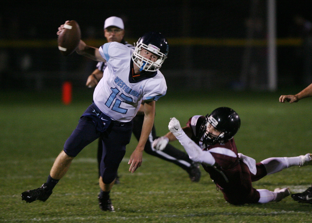 Westbrook quarterback Bailey Sawyer slips free from Greely's Alex Kroot in the second quarter Friday in Cumberland.