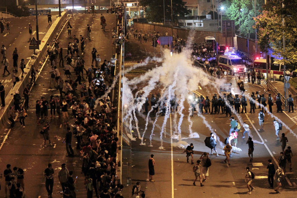 Riot police fire tear gas on student protesters occupying streets surrounding the government headquarters in Hong Kong early Monday. The Associated Press