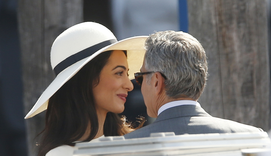 George Clooney and his wife Amal Alamuddin leave the municipal building after their civil marriage ceremony in Venice Monday. The Associated Press