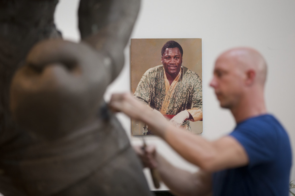 Layne works on a sculpture of boxing heavyweight champion Joe Frazier with a photo of the fighter in the background.