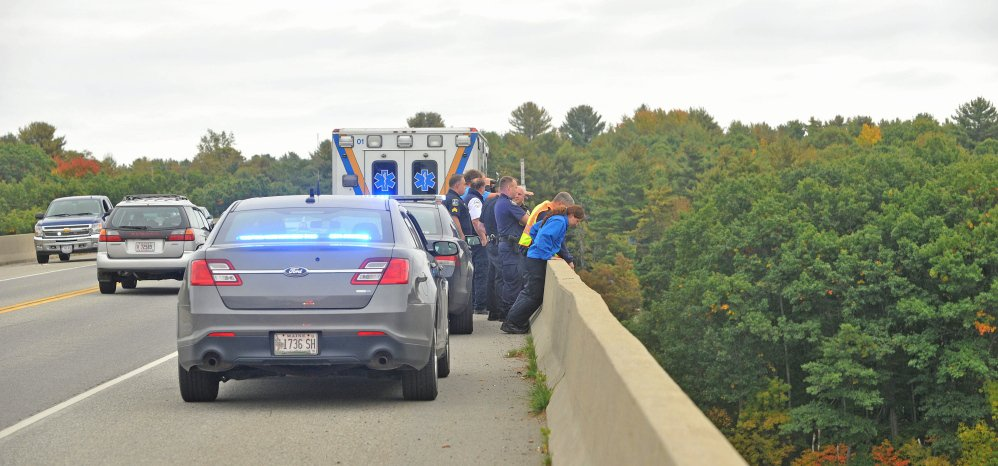 Rescue workers and police from Waterville and Winslow look for a woman who was reported to have jumped from Carter Memorial Bridge on the Waterville/Winslow town line Tuesday.