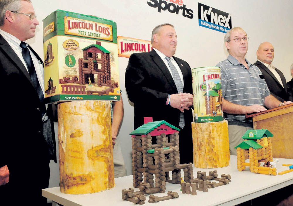 Gov. Paul LePage, center, listens Wednesday as Randy Dickers of Pride Manufacturing announces that the Burnham plant will now mill pieces for Lincoln Log toys. At left is Walt Whitcomb, commissioner of agriculture and at far right is Larry Fanelle of the K'NEX company.