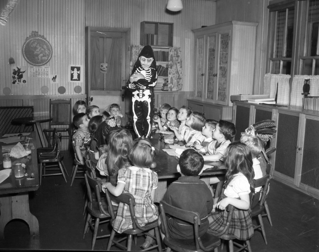 """Uncredited photo from the Oct. 31, 1939 Evening Express.  Original caption: """"Ugh. What a centerpiece for a party! Youngsters at the Sherman Street Kindergarten know, however, that the eerie skeleton is only William (Billy) DeNeill and that their teacher, Miss Helen C. Sullivan, helped the awesome figure to his elevated position. Celebrating Halloween around the table are Alvin Brown, Susan Brow, Rovert Robinson, Frances Anifant, Everett Robinson, Marilyn Levine, Robert Cook, Paul Kelly, Joyce Fuller, Roberta Singer, Jane Larsen, Alice Savage, Stanley Welch, Shirley Welch, Janette Shatz, Gerald Hegesty, Judith Smith, William Troubh, Sondra Caston and Norma Smith."""""""