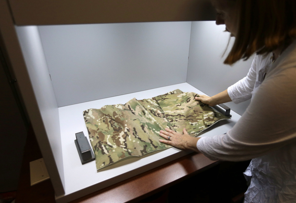 Clare King, of Providence, R.I., compares swatches of camouflage fabric in a shade box at Propel LLC, a textile technology research company, in Pawtucket, R.I. The shade box is used to  inspect camouflage designs and compare research fabrics to match a standard. King is president of Propel LLC.