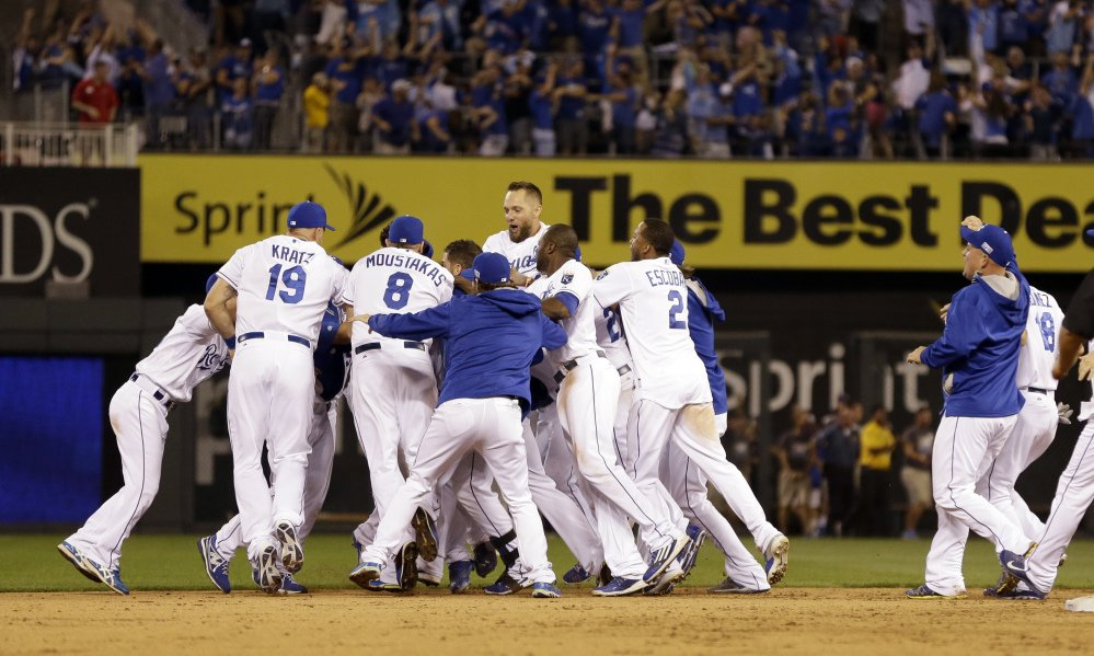 The Kansas City Royals mob teammate Salvador Perez after his walk-off single in the 12th inning to defeat the Oakland Athletics, 9-8. The Royals move on to play the Angels.