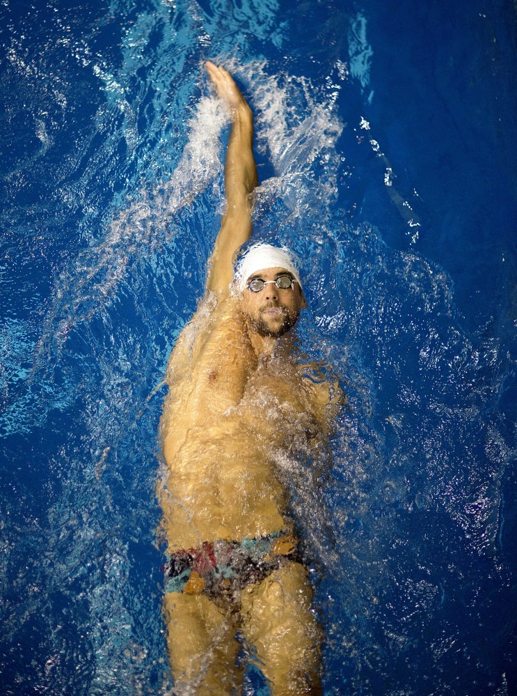 In this July 12, 2014, file photo, Michael Phelps warms up for the men's 100-meter backstroke at the Bulldog Grand Slam swim meet at the University of Georgia in Athens, Ga.