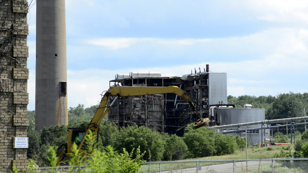 Heavy machinery chips away at what remains of the Great Northern Paper Co. mill in Millinocket.