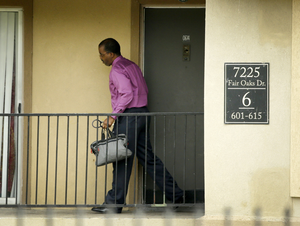 Dr. Christopher Perkins, medical director of the Health Authority with Dallas County Health and Human Services, walks out of an apartment unit at The Ivy Apartment Complex in Dallas on Thursday.