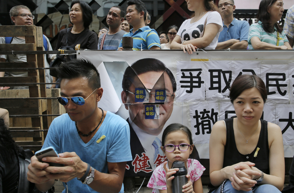 A pro-democracy protester, left, uses his smartphone while sitting in the street during a rally in Hong Kong on Thursday.