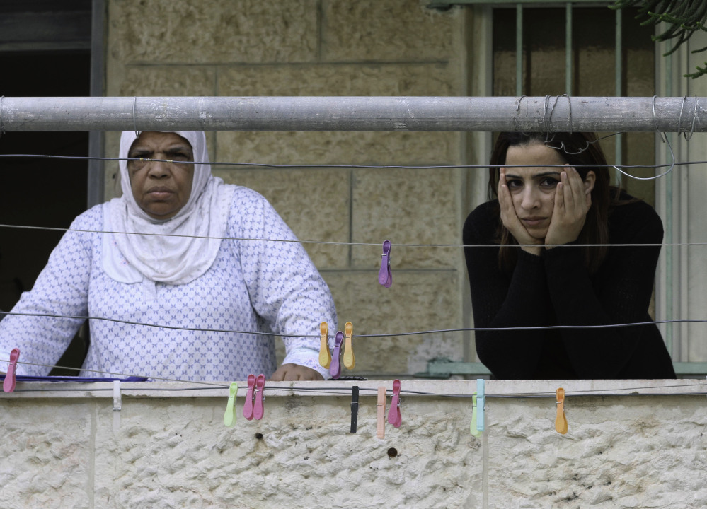 Palestinian women stand on their balcony overlooking a neighboring house that Jewish settlers moved into, in the Palestinian neighborhood of Silwan, east Jerusalem. About 500 Jews live in the area, and the newly purchased homes will allow for 200 more.