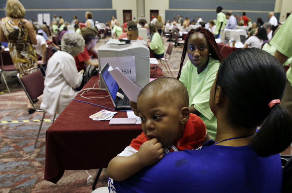 Fatuma Kamara holds her 11-month-old as she gets help from Kristanna Brown in filing for unemployment benefits during a mass session for newly laid-off casino workers last month in Atlantic City, N.J.
