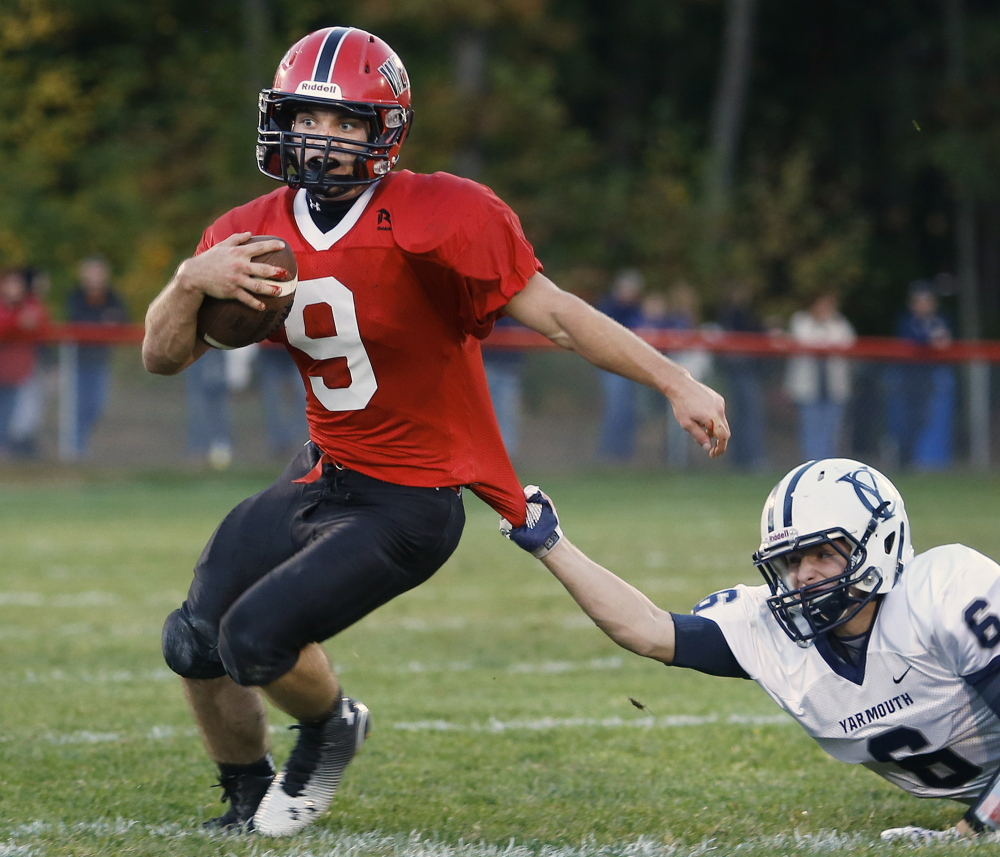 Chris Carney of Wells attempts to break away from Jack Snyder of Yarmouth during the first half of Wells' 21-14 victory Thursday night. Carney gained 145 yards in the first half and finished with 175, plus a touchdown.