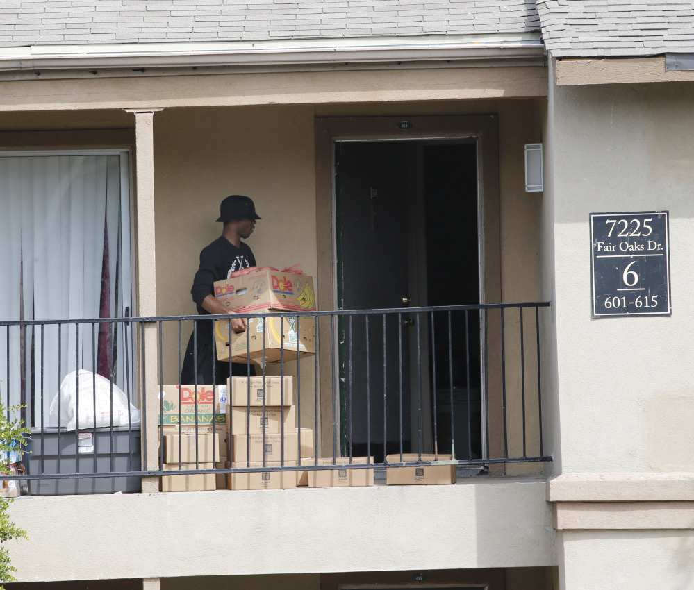 A young man retrieves food supplies left by the North Texas Food Bank and the Red Cross on the front stoop of an apartment at The Ivy Apartments complex, Thursday, Oct. 2, 2014, in Dallas, at The Ivy Apartments complex, Thursday, Oct. 2, 2014, in Dallas, where Thomas Eric Duncan, the Ebola patient who traveled from Liberia to Dallas last week, was staying.  Dallas County officials have ordered family members who had contact Duncan, quarantined in their home to prevent the spread of disease. (AP Photo/The Dallas Morning News, David Woo)  MANDATORY CREDIT; MAGS OUT; TV OUT; INTERNET USE BY AP MEMBERS ONLY; NO SALES