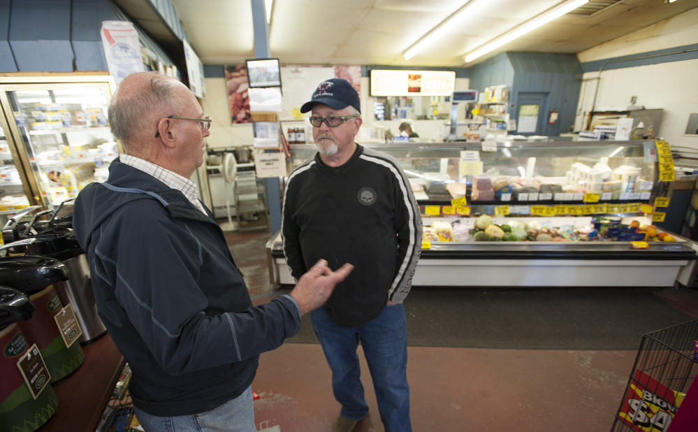 Retired Verso Paper mill worker Vernard Coffin, left, and current employee Stephen Bowden talk Thursday about the mill closure in front of the deli at Toziers Market on Main Street in Bucksport.