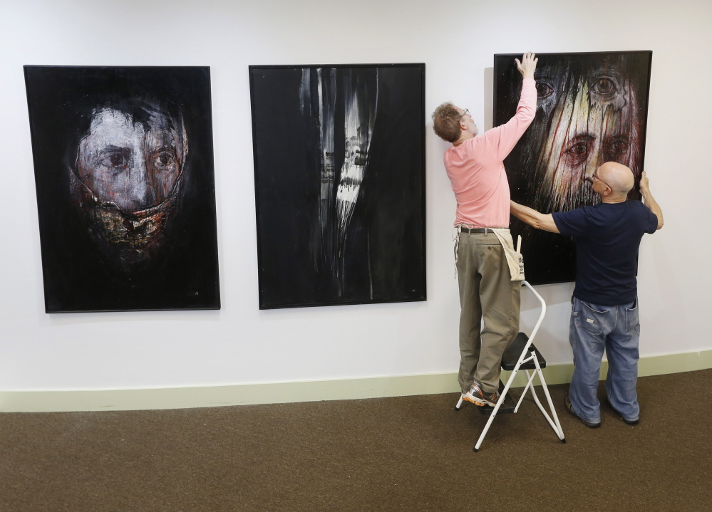 """Leonard Meiselman, right, hangs his paintings with help from fellow artist George Mason for """"The Dilemma of Memory"""" at the Holocaust and Human Rights Center of Maine.  Derek Davis/Staff Photographer"""