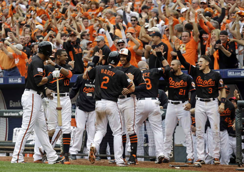 The Baltimore Orioles' J.J. Hardy (2) celebrates with teammates after scoring the go-ahead run against the Detroit Tigers in the eighth inning of Game 2 of the AL Division Series in Baltimore on Friday.