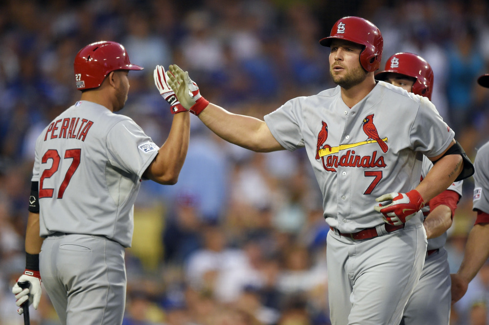 The St. Louis Cardinals' Matt Holliday is greeted by teammate Jhonny Peralta after hitting a three-run home run against the Los Angeles Dodgers in an eight-run seventh inning of Game 1 of the NL Division Series on Friday in Los Angeles. The Cardinals rallied for a 10-9 victory.