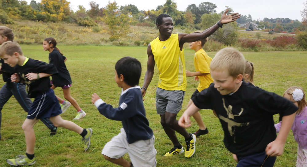 Moninda Marube of Auburn encourages children to run with him at Auburn Middle School. Marube, a distance runner who is originally from Kenya, will be running in the Maine Marathon on Sunday.