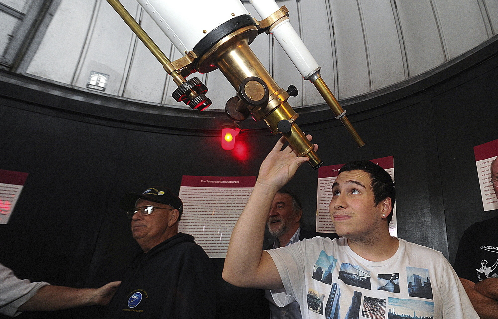 Colton Botelho, a senior at B.M.C. Durfee High School in Fall River, Mass., peers through the eyepiece of the school's newly restored telescope.