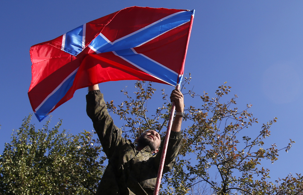 A pro-Russian rebel places a flag of the self-proclaimed Federal State of Novorossiya atop his truck before fighting began Friday near the airport in Donetsk, eastern Ukraine.