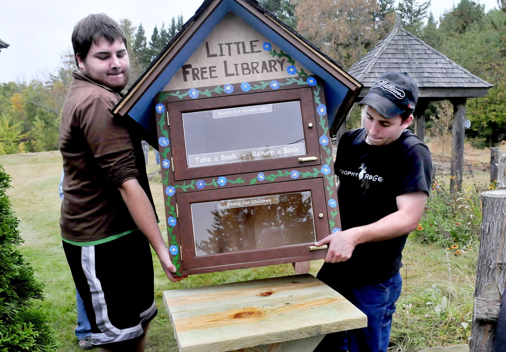 Thomas Ciarlante, left, and Brett Skelly, volunteers from Unity College, place a Little Free Library, where people can donate and borrow books, at Triplet Park in Unity on Saturday.