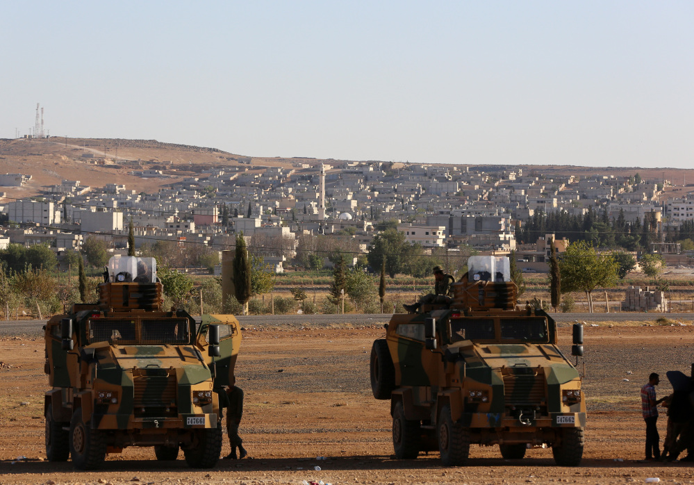 Turkish soldiers take up a defensive position a few hundred meters from their border with Syria as fighting intensified on Saturday between Syrian Kurds and Islamic State forces in nearby Kobani, Syria.