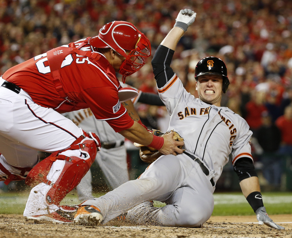 Buster Posey of the San Francisco Giants is tagged out by Washington catcher Wilson Ramos in the ninth inning of San Francisco's 2-1 victory in 18 innings Saturday night.