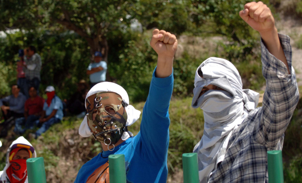 Masked students raise their fists as they block a main highway in Chilpancingo, Mexico, Sunday.