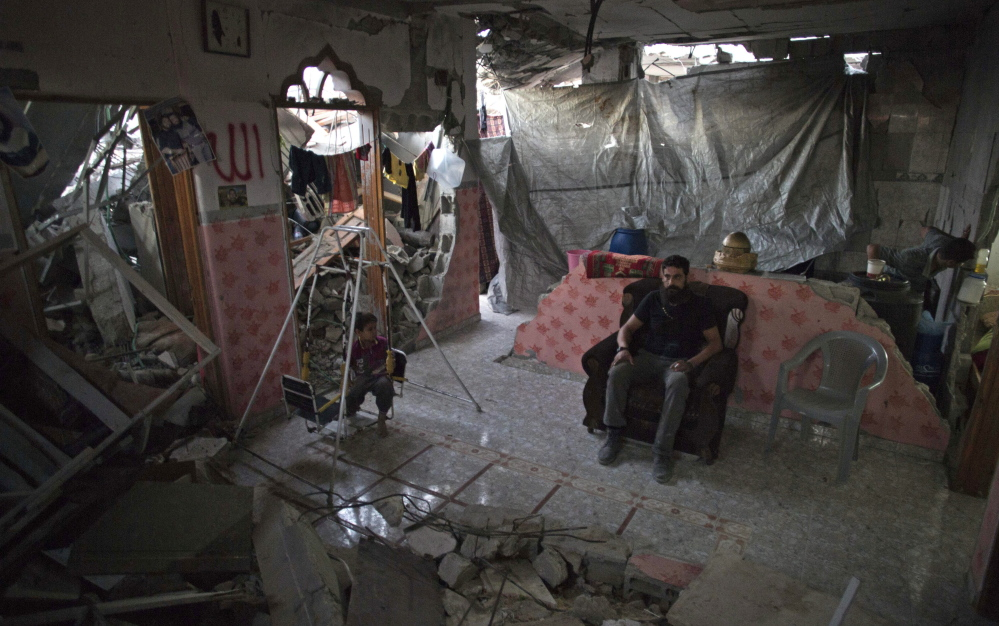 Palestinian Madi Hasanein sits next to his son while he swings in what is left of  their house in Gaza City. Thousands of people whose homes were destroyed or damaged in the Israel-Hamas war still live in classrooms, storefronts and shelters.