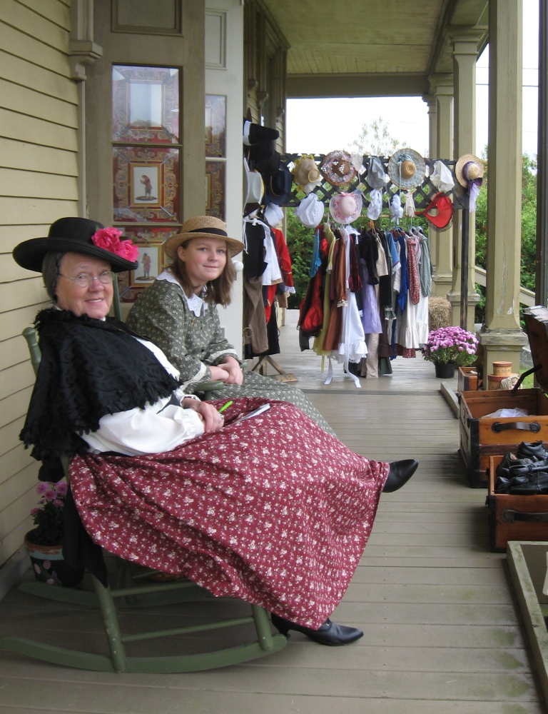 Rita St. Clair, left, and Hayley Rose Hatfield dress in clothes from the Caroline's Closet room at the  Washburn-Norlands Living History Center in Livermore. Attendees of the center's fall festival are invited to try on some fashions of yesteryear during Saturday's festivities.